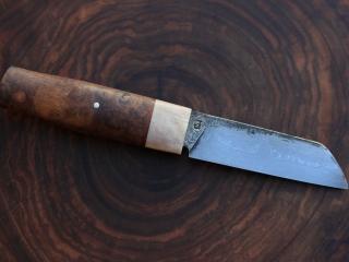 Lame en damas 300 couches 15N20/90MCV8, manche en bois de renne et loupe de chêne, intercalaire en écorce de bouleau. Etui en cuir sur mesure, rétention parfaite avec « clic »